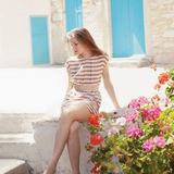 Fashionable young woman posing in dress. In the southern town of Europe on a summer day Royalty Free Stock Photo