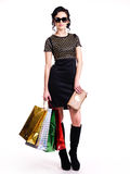 Fashionable young woman with purchases in hands. Stock Photos