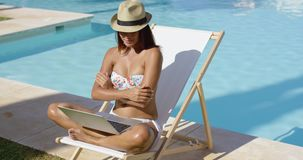 Fashionable young woman relaxing at the pool stock footage