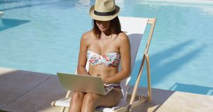 Fashionable young woman relaxing at the pool. Sitting cross-legged in a bikini and trendy hat on a deck chair working on a laptop stock footage
