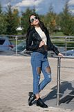 Fashionable young woman in rock style clothes, black leather jacket, blue jeans, tights in a grid under battered jeans Stock Images