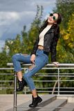 Fashionable young woman in rock style clothes, black leather jacket, blue jeans, tights in a grid under battered jeans Stock Image