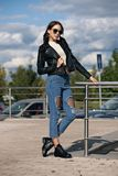 Fashionable young woman in rock style clothes, black leather jacket, blue jeans, tights in a grid under battered jeans Royalty Free Stock Photos