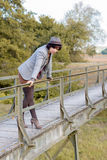 Fashionable young woman on a rustic footbridge Stock Image