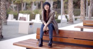 Fashionable young woman sitting waiting on a bench. Fashionable young woman in a trendy modern outfit and boots sitting on an outdoor wooden bench in a park stock video footage