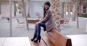 Fashionable young woman sitting waiting on a bench. Fashionable young woman in a trendy modern outfit and boots sitting on an outdoor wooden bench in a park stock video