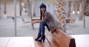 Fashionable young woman sitting waiting on a bench Stock Images