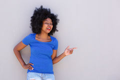 Fashionable young woman smiling and pointing to wall. Portrait of fashionable young woman smiling and pointing to wall Stock Photography
