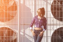 Fashionable young woman in sunglasses, lilac short windbreaker and jeans. on the background of large air conditioners. Women`s fa Royalty Free Stock Photo