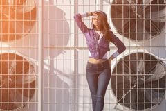 Fashionable young woman in sunglasses, lilac short windbreaker and jeans. on the background of large air conditioners. Women`s fa Royalty Free Stock Images