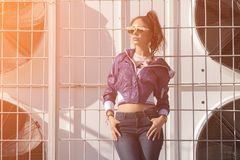Fashionable young woman in sunglasses, lilac short windbreaker and jeans. on the background of large air conditioners. Women`s fa Stock Photos