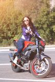 Fashionable young woman with sunglasses, lilac short windbreaker and jeans with a beautiful body on a red sports bike royalty free stock photos