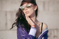 Fashionable young woman in sunglasses, lilac short windbreaker and jeans. Sits on a concrete structure, bare shoulder Royalty Free Stock Photos