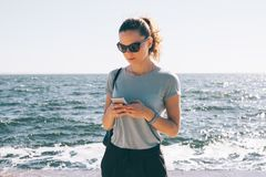Fashionable young woman in sunglasses standing. Texting on the background of sea and sun flare. Female wearing blue t-shirt and black pants using smart phone on royalty free stock photos