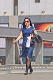 Fashionable young woman walks at Xidan commercial area, Beijing, China. BEIJING-APRIL 28, 2016. Fashionable woman in city center. China's economy, boosted by Royalty Free Stock Photos