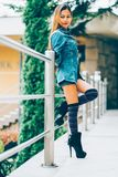 Fashionable young woman wearing blue jeans jacket with the high hills and long stripe knee socks. autumn fashion style Stock Image