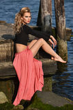 Fashionable young woman wearing cropped top and maxi skirt posing outdoors at boat marina. Stock Photo