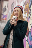 Fashionable young woman with wool hat drinks coffee in the street on a cold day Royalty Free Stock Image