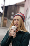 Fashionable young woman with wool hat drinks coffee in the street on a cold day Stock Photos
