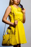 Fashionable young woman in yellow dress with handbag and sunglasses Stock Photos
