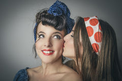 Fashionable young women having friendly kiss. Portrait of two happy young women in retro clothes, one kissing the cheek of her friend, studio background royalty free stock photo