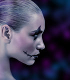 Fashionable zombie girl. Side view of zombie girl with creepy makeup on blue and purple blurry background, night of horror, time for witches and vampire royalty free stock images