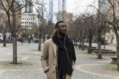 Fashionably Dressed Black Man in Beige Coat Standing in City