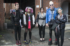 Fashionably-dressed group of young people standing near the wall. Stock Photo