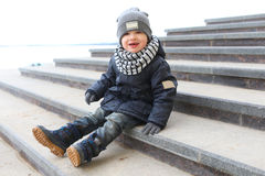Fashionably dressed little boy sitting on stairs outdoors in spr Royalty Free Stock Image
