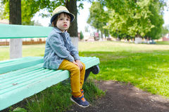 Fashionably dressed little boy in straw hat sits on bench in gro Royalty Free Stock Images