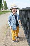 Fashionably dressed little boy in straw hat walks in summer Royalty Free Stock Photography