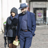 A fashionably dressed man and woman in blue suits and hats walk down the street. Stock Image