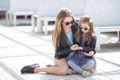 Fashionably dressed mother and daughter on the street in the spring Royalty Free Stock Images