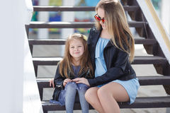 Fashionably dressed mother and daughter on the street in the spring Royalty Free Stock Photo