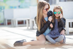Fashionably dressed mother and daughter on the street in the spring Stock Images