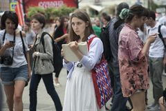 Fashionably dressed people walk downtown. Moscow, RUSSIA - June 12, 2019: Fashionably dressed people walk downtown. Girl draws in the album stock photography