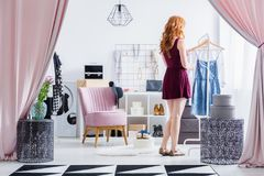 Fashionably dressed woman in closet. Fashionably dressed woman choosing clothes while standing in walk-in closet with pink chair royalty free stock images