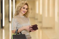 Fashionably dressed woman with shopping bags in mall. Young stylish girl with wallet. Shopping concept Royalty Free Stock Photography