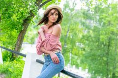 Fashionably dressed young woman on the street on a sunny evening. Beautiful girl in jeans and small hat is standing and looking stock photography