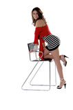 Fashionably Pirate. Pretty young Mexican woman in a red wrap, black and white striped mini dress with pearls around her wrist and kneeling on a chair Stock Image