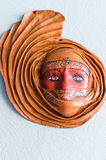 Fashioned from clay mask. Hanging on a white wall stock photography