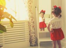 Fashionista del niño de la niña que mira en el espejo en casa fotografía de archivo libre de regalías