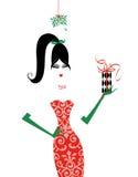 Fashionista elegante sotto il vischio con un regalo di Natale Immagini Stock Libere da Diritti
