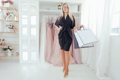 Fashionista lifestyle woman evening gown boutique. Fashionista lifestyle. Luxury evening gown boutique. Sophisticated interior. Woman standing with white mockup stock photo
