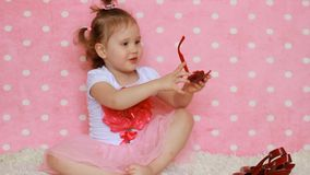 Fashionista. A little girl lady with a red bag , glasses sunshine and shoes. Funny child. Pink background. Glamour stock footage