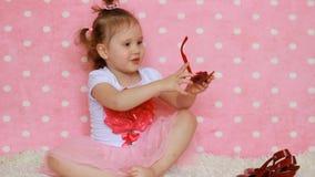 Fashionista Una signora della bambina con una borsa rossa, i vetri sole e le scarpe Bambino divertente Fondo rosa fascino stock footage