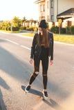 Fashionly gekleed meisje die op Skateboard schaatsen, in openlucht royalty-vrije stock afbeelding