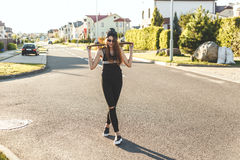 Fashionly a habillé la fille de patineur posant avec le conseil sur la route urbaine Temps de coucher du soleil Photos stock