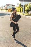 Fashionly a habillé la fille de patineur posant avec le conseil sur la route urbaine Temps de coucher du soleil Photographie stock