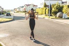 Fashionly ubierał łyżwiarki dziewczyny pozuje z deską na miasto drodze ujawnienia zawodnik bez szans zmierzchu czas Zdjęcia Stock